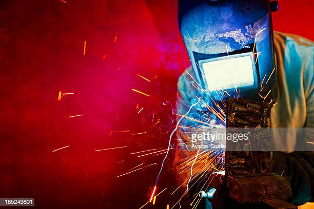 welder welding, sparks fly. - welding stock photos and pictures
