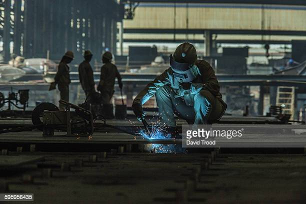 Welder working at a ship building yard in China.
