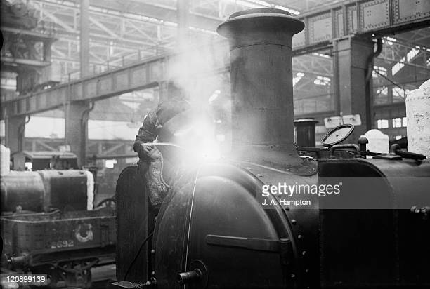 A welder working on a locomotive at the GWR works at Swindon Wiltshire 20th April 1932
