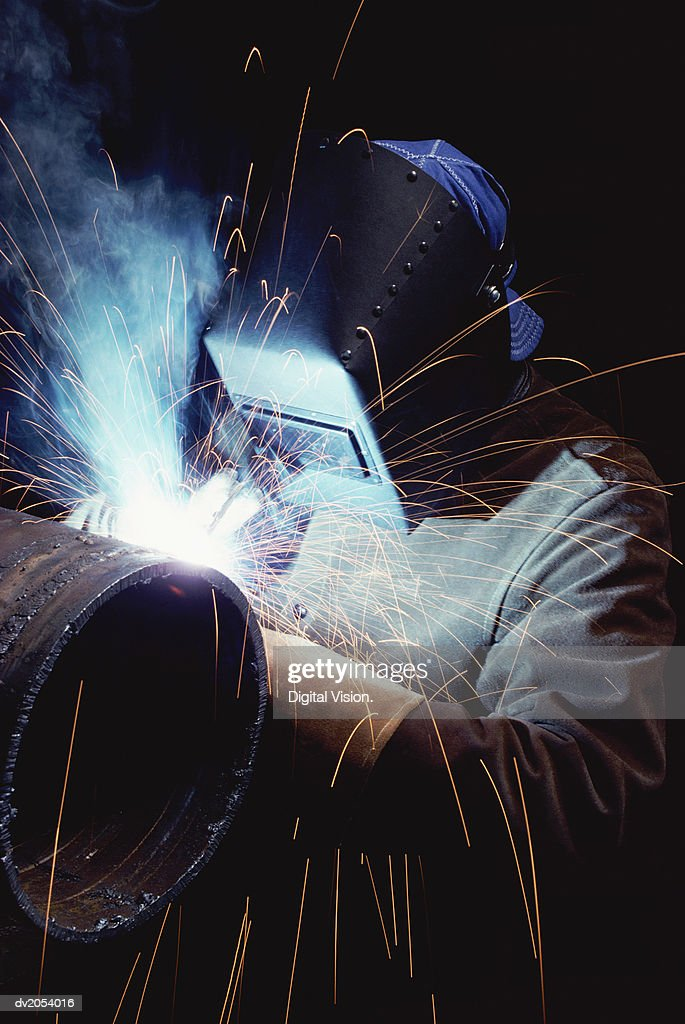 Welder Working on a Metallic Cylinder : Stock Photo