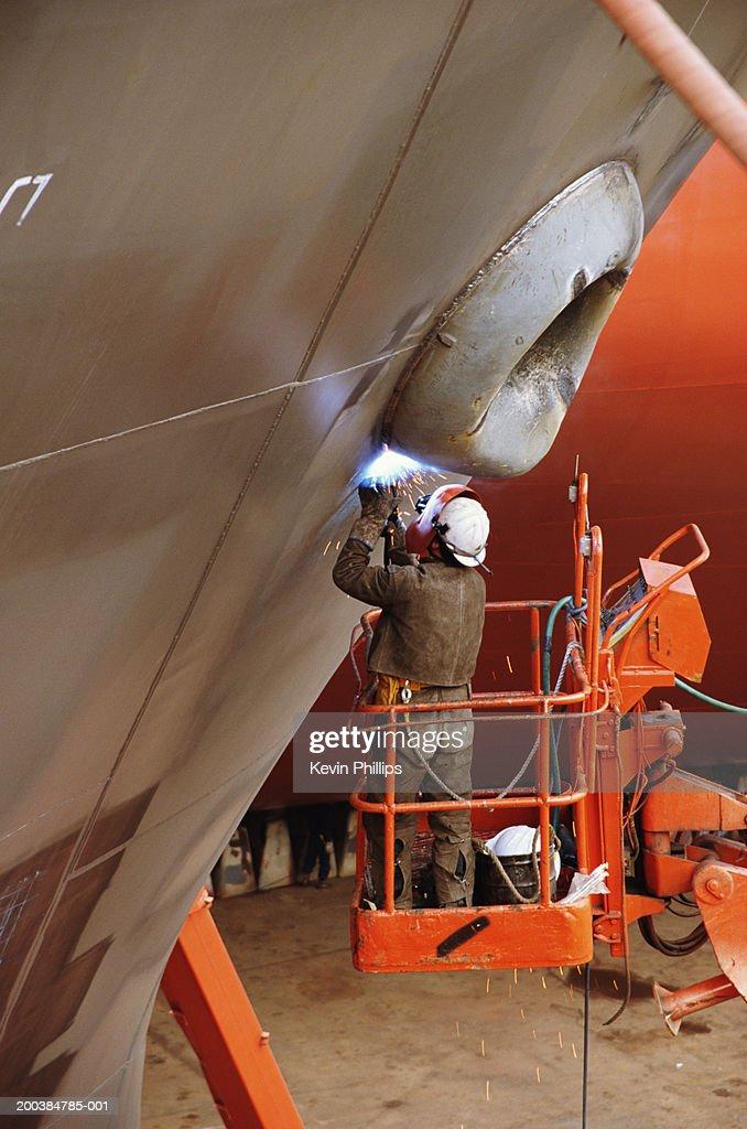 Welder working on side of ship in dry dock, standing on cherry-picker : Stock Photo