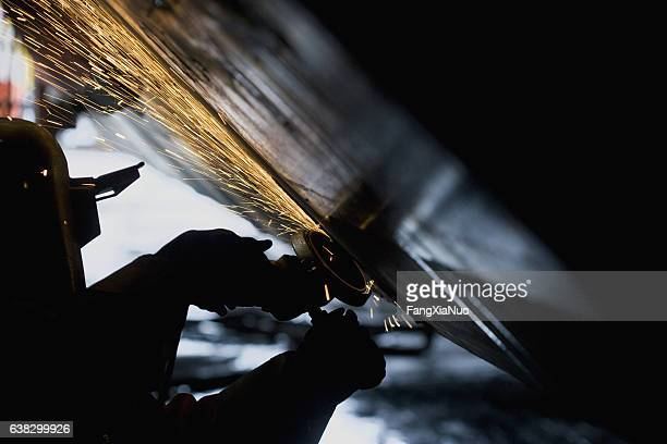 welder working with grinder on side of a boat hull - watervaartuig stockfoto's en -beelden