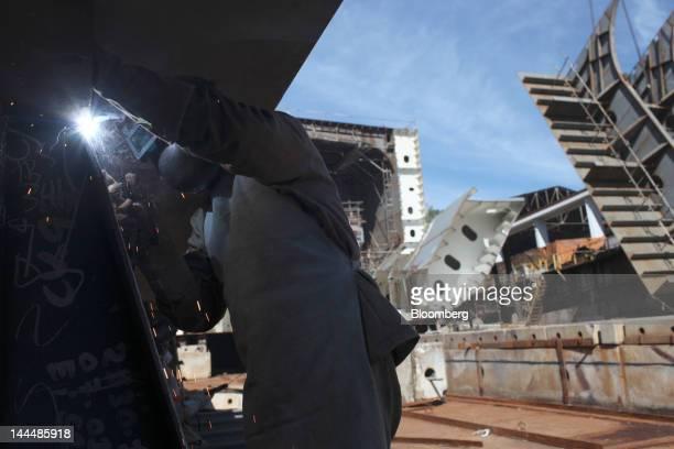 A welder works on a Petroleo Brasileiro SA oil tanker under construction at the Maua SA shipyard in Niteroi Brazil on Thursday May 10 2012 The...