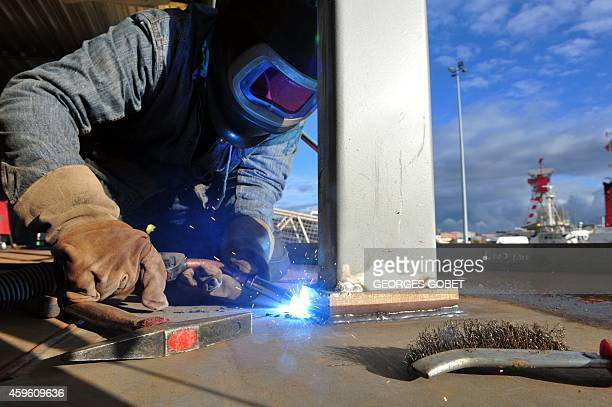 A welder works on November 26 2014 on the Loire Princesse riverboat during its unveiling in the western port French port of SaintNazaire le 26...
