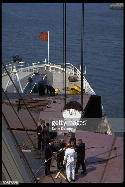 Welders fitting QE2 for helicopter pad before voyage to Falklands