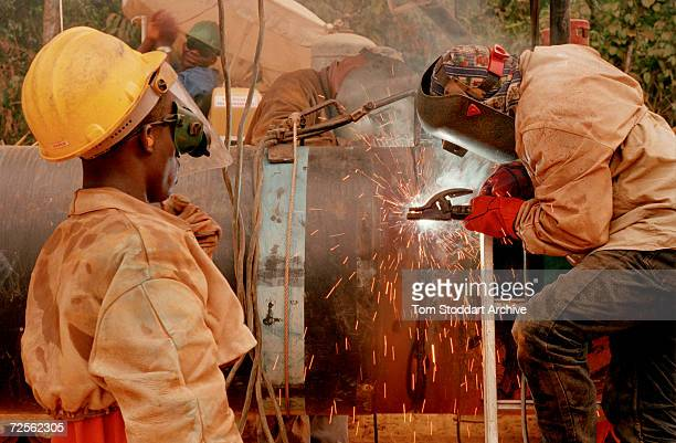 Welders join 40 foot sections of pipeline which will carry oil from the landlocked oil fields of Chad through the jungles of Cameroon to the Gulf of...
