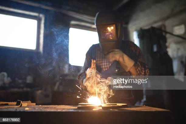 welding in smithy - in flames i the mask stock pictures, royalty-free photos & images
