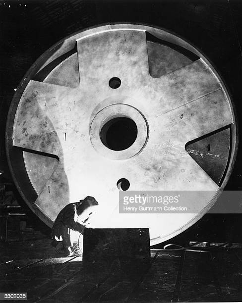 A welding operator dwarfed by his steel target at work on the outside rim of a large rotating motor part