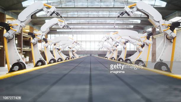 welding robots and conveyor belt in automated factory - industry stock pictures, royalty-free photos & images