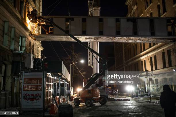 Welding team cuts the support beams to a 17-ton pedestrian bridge before a crane removes the span between the historic landmarked Polhemus Building,...