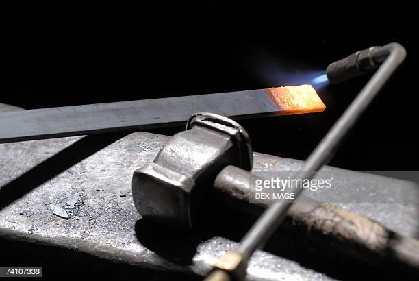 Welding torch heating an iron rod