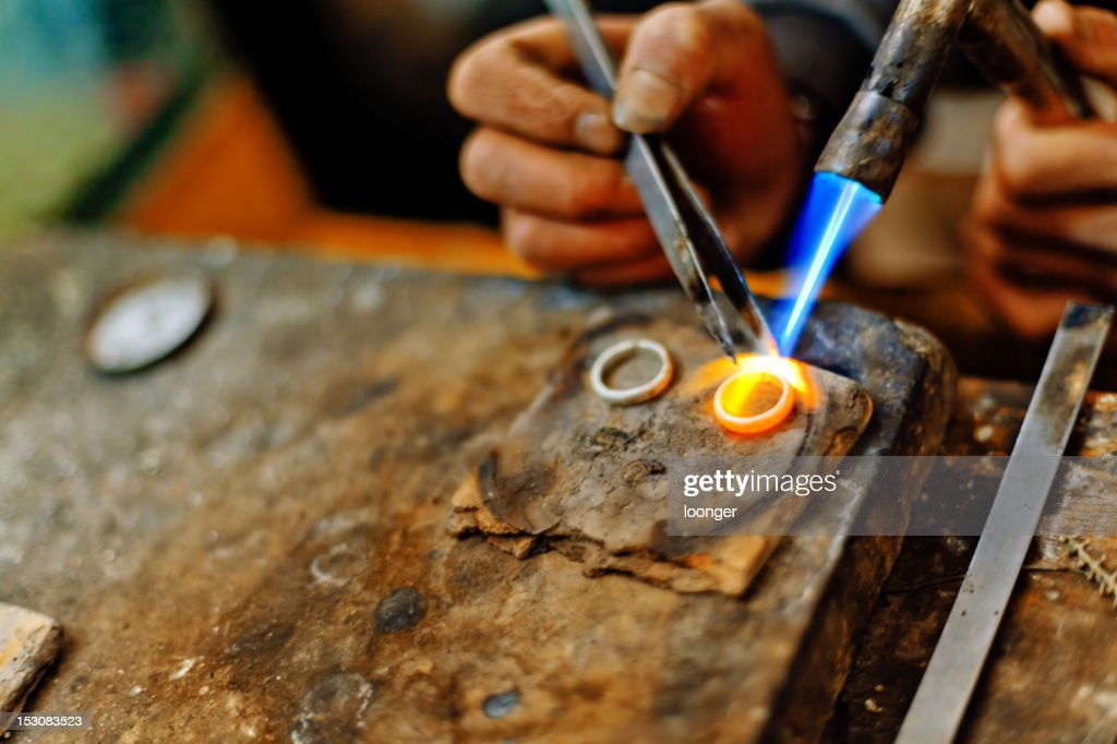 Welding torch melting the silver rings : Stock Photo