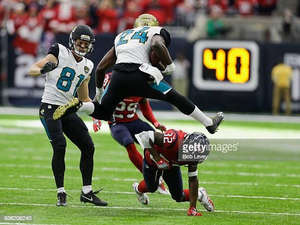 Weldon of the Jacksonville Jaguars hurdles Robert Nelson of the Houston Texans as Bryan Walters and Andre Hal look on at NRG Stadium on December 18,...