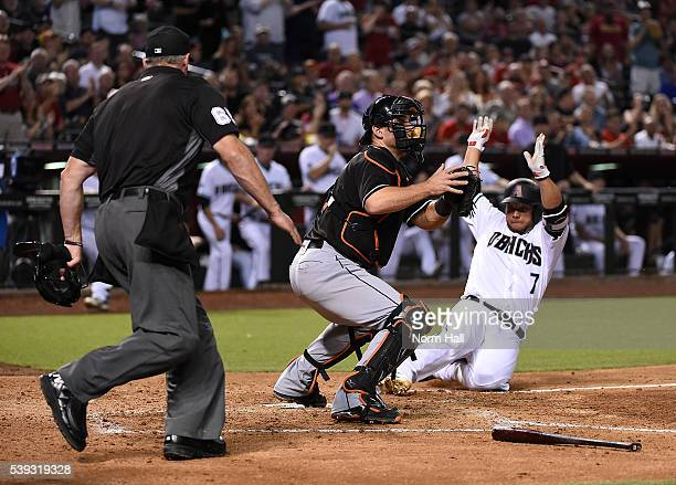 Welington Castillo of the Arizona Diamondbacks safely slides into home on a double by teammate Jake Lamb during the fifth inning as catcher Jeff...