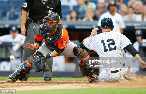 Welington Castillo of the Baltimore Orioles waits for the throw as Chase Headley of the New York Yankees slides home with a run in the first inning...