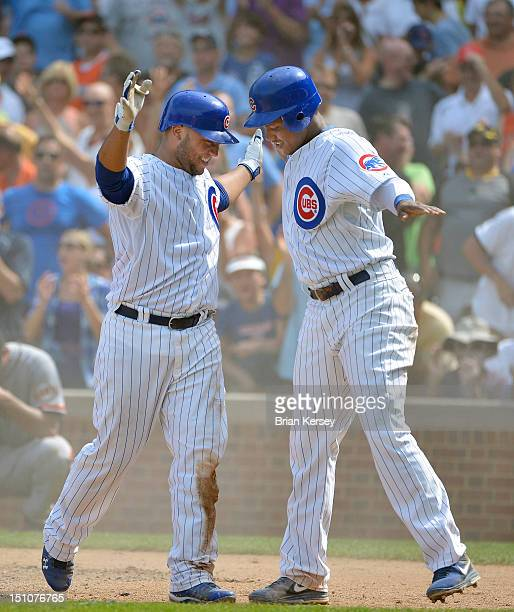 Welington Castillo of the Chicago Cubs celebrate after the pair scored when Castillo hit an RBI double scoring Castro and then scored himself on a...