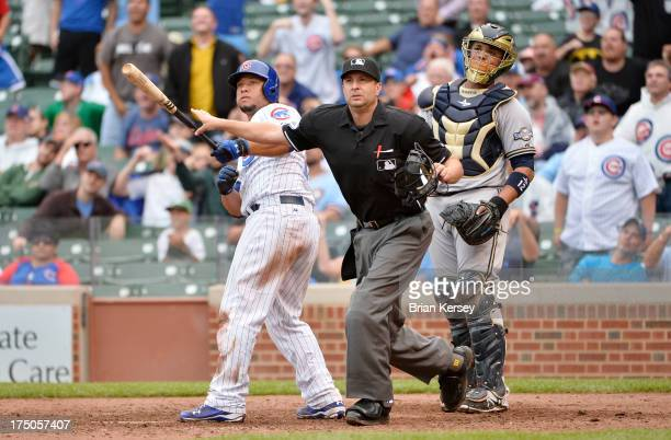Welington Castillo of the Chicago Cubs home plate umpire Jim Reynolds and catcher Martin Maldonado of the Milwaukee Brewers watch to see if a long...