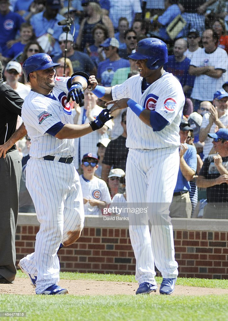 Welington Castillo (L) of the Chicago Cubs is greeted by Starlin Castro #13 after hitting a two-run homer against the Milwaukee Brewers during the fourth inning on September 1, 2014 at Wrigley Field in Chicago, Illinois.