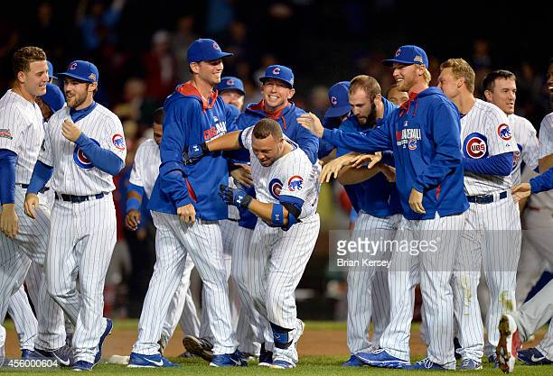Welington Castillo of the Chicago Cubs is mobbed by his teammates after hitting a gamewinning RBI single scoring teammate Anthony Rizzo during the...