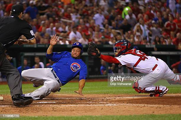 Welington Castillo of the Chicago Cubs scores a run against Tony Cruz of the St Louis Cardinals in the seventh inning at Busch Stadium on August 9...