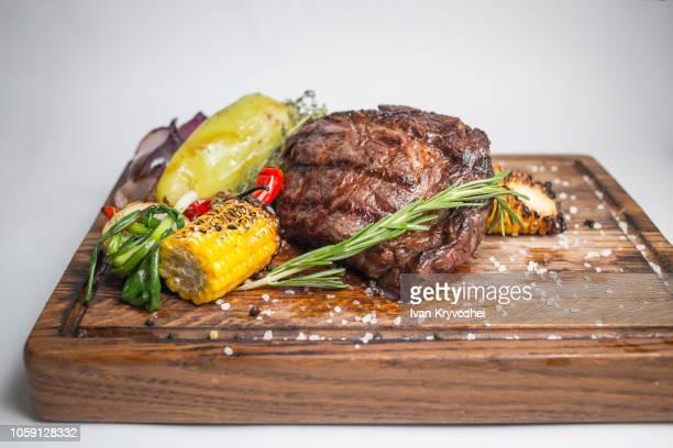 well done steak with grilled vegetables on wooden board - mais gemüse stock-fotos und bilder