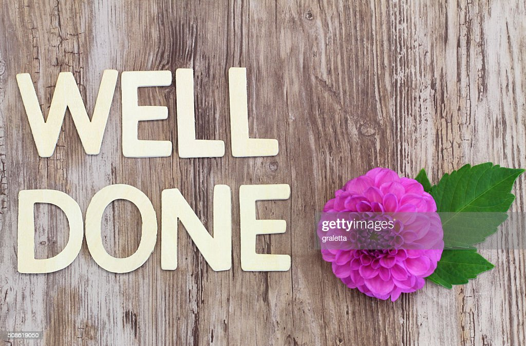 Well done written with wooden letters on rustic surface, dahlia : Stock Photo
