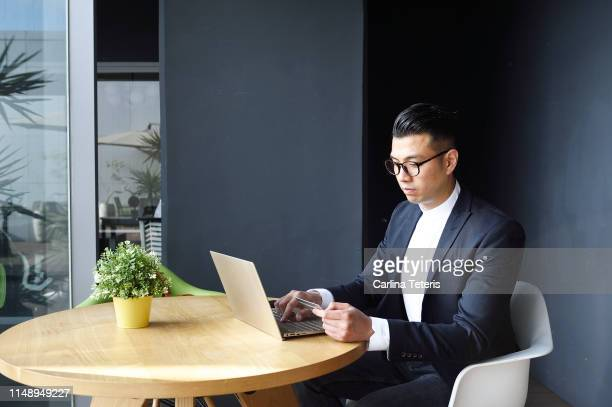 well dressed asian man making an online purchase - マオカラー ストックフォトと画像