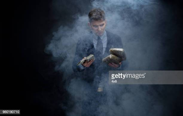 Well dressed businessman holding a brick of weed and cash