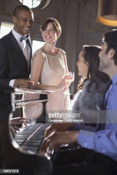 Bien habillés amis jouant du piano dans le salon