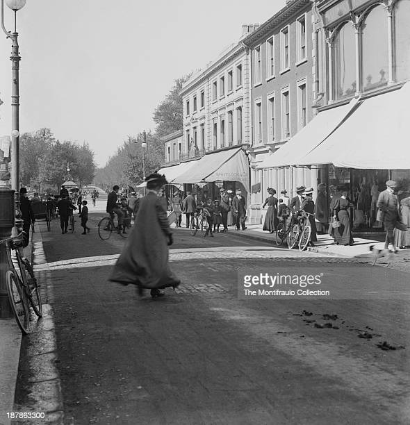Well dressed lady walking down a bustling Bedford High Street Bedfordshire England circa 1900