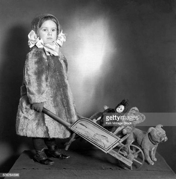 Well dressed little girl poses with a toy wheelbarrow of her favorite toys in a studio portrait from the early 20th century.