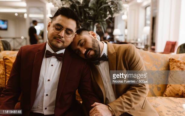 well dressed male couple in a hotel - images stock pictures, royalty-free photos & images