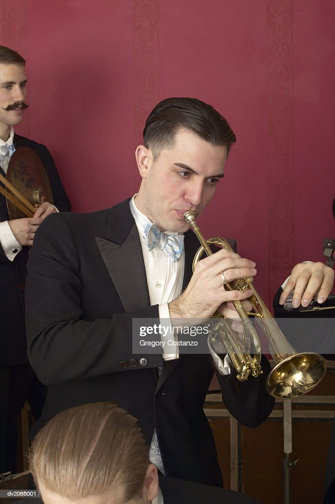 Well Dressed Male Musician Plays the Trumpet in a Jazz Band : Stock Photo