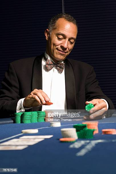Well dressed man contemplating bet at casino table