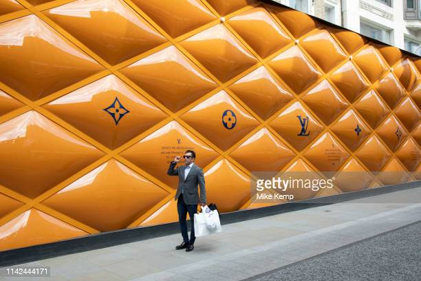 Well dressed man passes yellow temporary hoarding covering exclusive clothes shop window Louis Vuitton on New Bond Street in Mayfair London England...