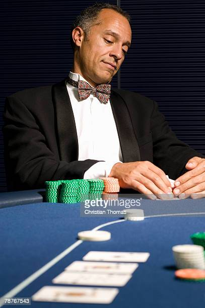 Well dressed man peeking at hand of cards at casino table