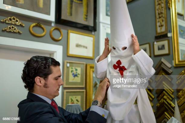 Well dressed man preparing a boy to participate in one of the processions held in Seville during Easter