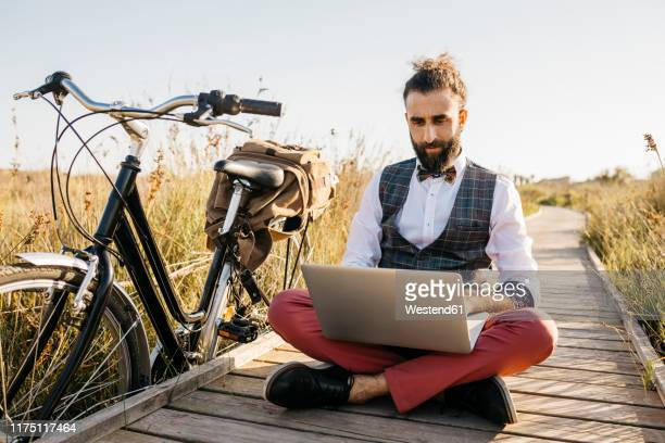 well dressed man sitting on a wooden walkway in the countryside next to a bike using laptop - カタルーニャ独立運動 ストックフォトと画像
