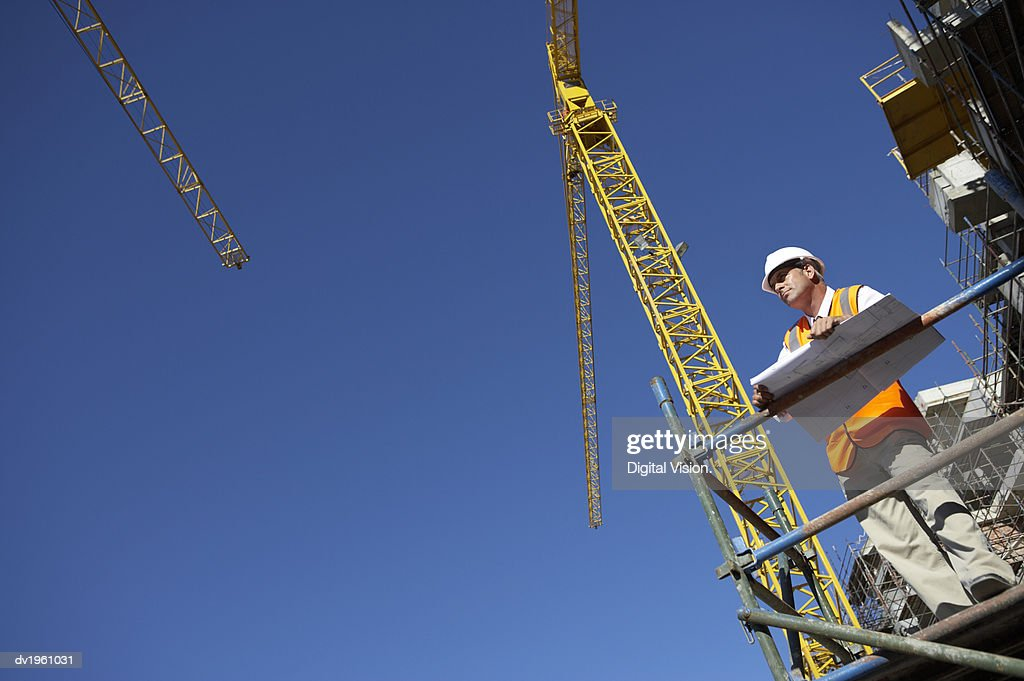 Well Dressed Man Standing on a Scaffolding Platform Holding Blueprints : Stock Photo