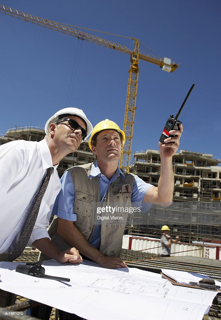 Well Dressed Man Wearing Sunglasses Standing Side by Side with a Building Site Foreman, who is Pointing with a Walkie Talkie : Stock Photo