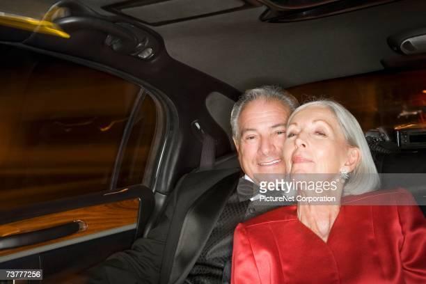 well dressed senior couple in limousine - abendkleid stock-fotos und bilder