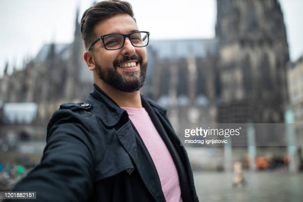 よく服を着た観光客は、ケルン、ドイツの大聖堂の前で自分撮りを取ります - ケルン市 ストックフォトと画像