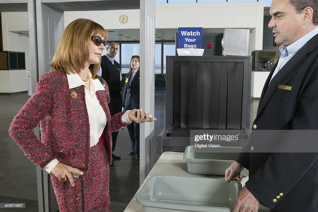 Well Dressed Woman Looking Impatiently at an Airport Customs Officer : Stock Photo