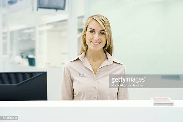 Well dressed woman standing behind counter, smiling at camera, portrait