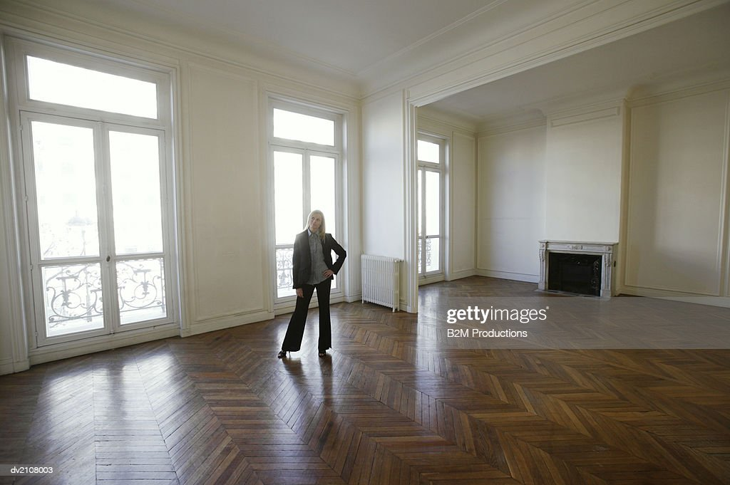 Well Dressed Woman Standing in a Large Empty Room with a Wooden Floor : Stock Photo