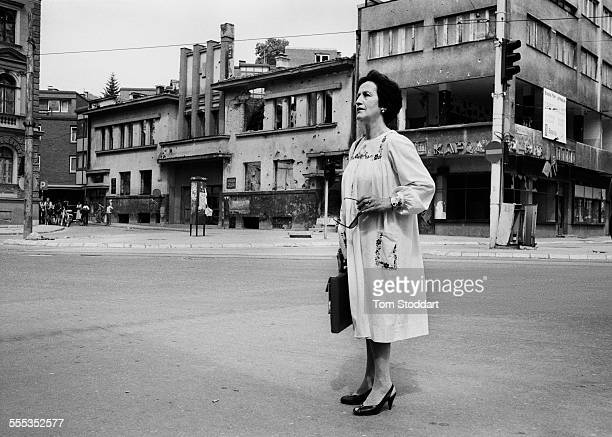 Well dressed woman waits for the shooting to stop before running across 'Sniper Alley' during the siege of Sarajevo in 1995. Many citizens have been...