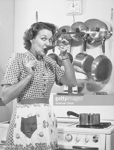 Well dressed woman w/apron in the kitchen taste testing her creation 1952
