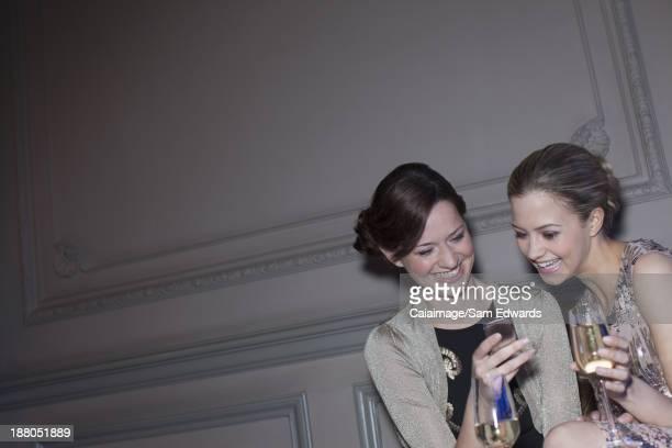 Bien habillée Femme buvant champagne et en regardant de téléphone cellulaire