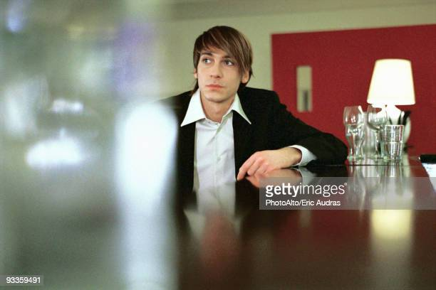 Well dressed young man leaning on bar, looking away