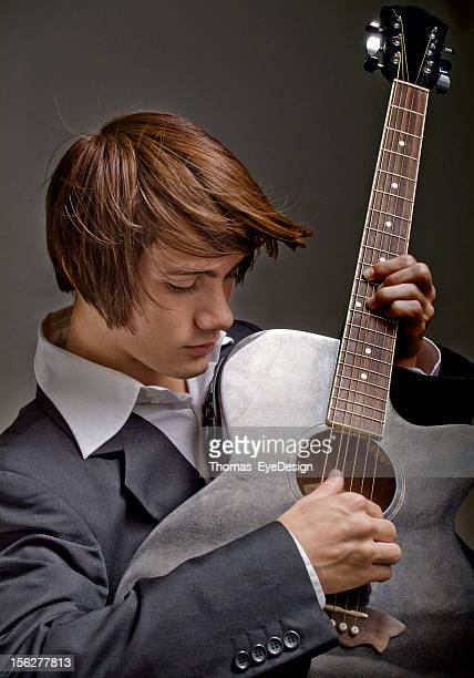 Well Dressed Young Man Playing the Guitar